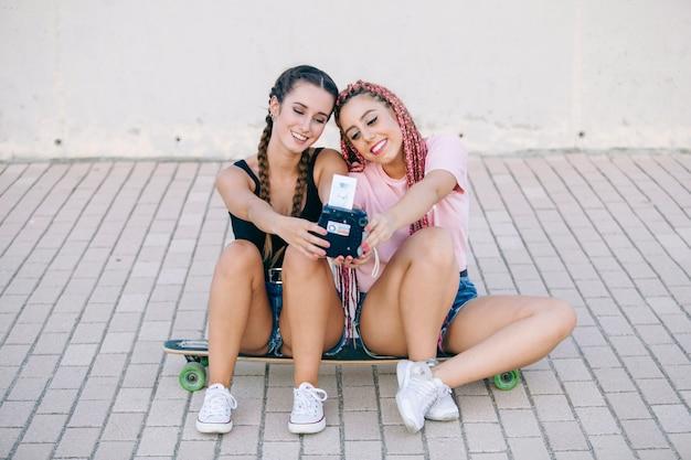 Друзья подростка сидя на скейтборде держа фотографию