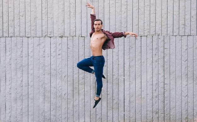 ジーンズの服でジャンプを実行する若い男性ダンサー