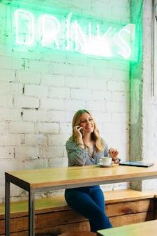Молодая жизнерадостная женщина разговаривает по телефону на перерыв