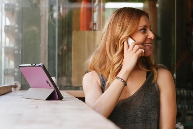 Жизнерадостная женщина разговаривает по мобильному телефону в кафетерии
