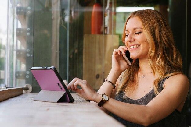 Жизнерадостная женщина разговаривает по мобильному телефону и использует современные технологии