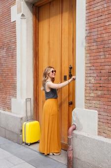 街でスーツケースを運ぶ彼女の新しいアパートを呼び出す女性