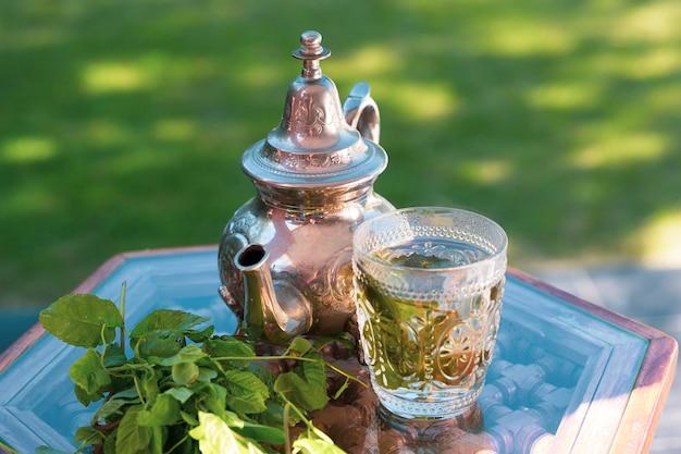 伝統的なトレイにモロッコの冷たい緑のハーブティー
