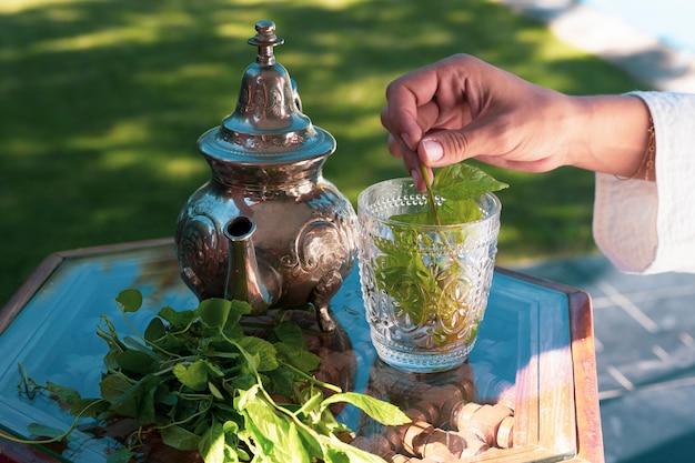 伝統的な方法で銀のティーポットを注いだモロッコのグリーンハーブティー