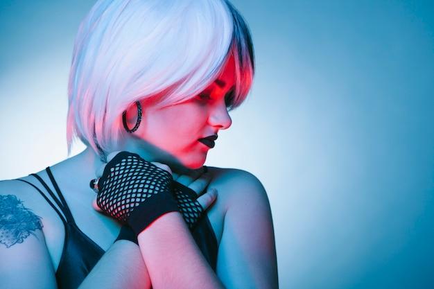 Крупным планом готической молодой женщины, изолированных на синей стене