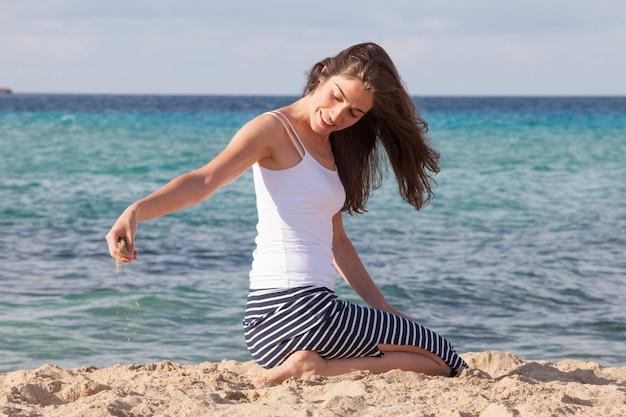 ビーチの砂で遊ぶ若い女性