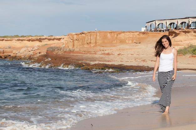 海岸で裸足で歩く若い陽気な女性