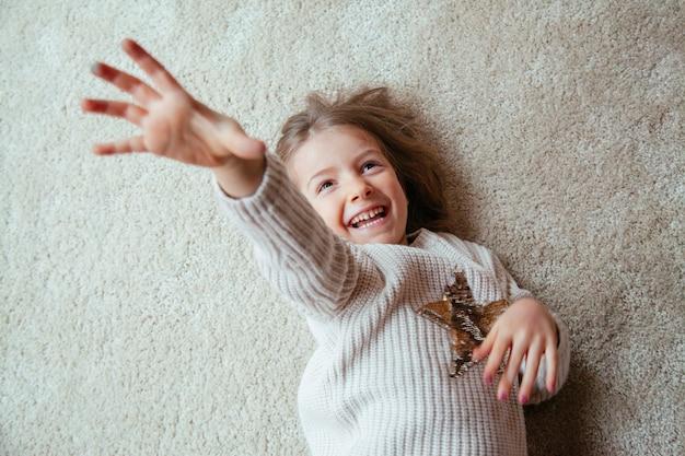 くすぐりが付いている床に小さな金髪の子供
