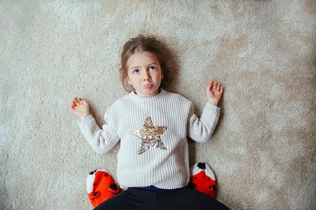 Маленький грустный ребенок на полу, играя с мамой