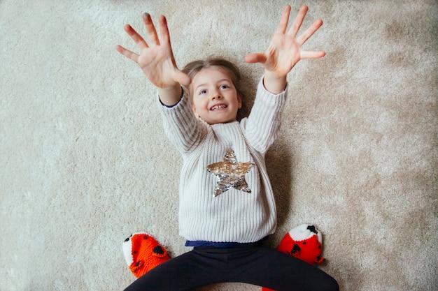 Маленький ребенок пытается щекотать маму на ковре