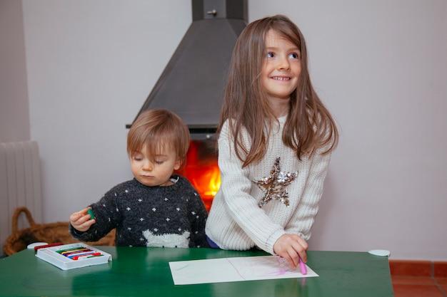Братья и сестры играют дома с цветными карандашами