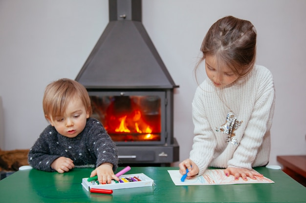 Братья и сестры играют дома с разноцветными карандашами возле костра