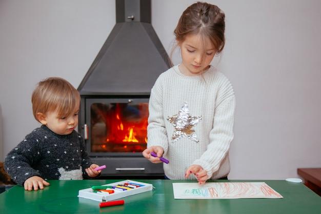 兄と妹がクレヨンで絵を描く