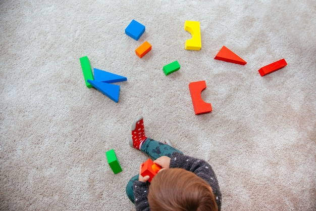 Белокурый маленький малыш играет с цветными структурами