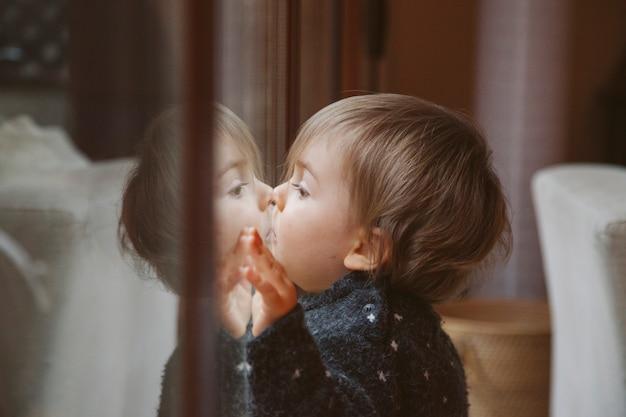 Непослушный маленький мальчик играет на окнах