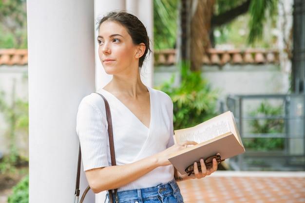 Спокойная женщина думает о книге, которую она читает