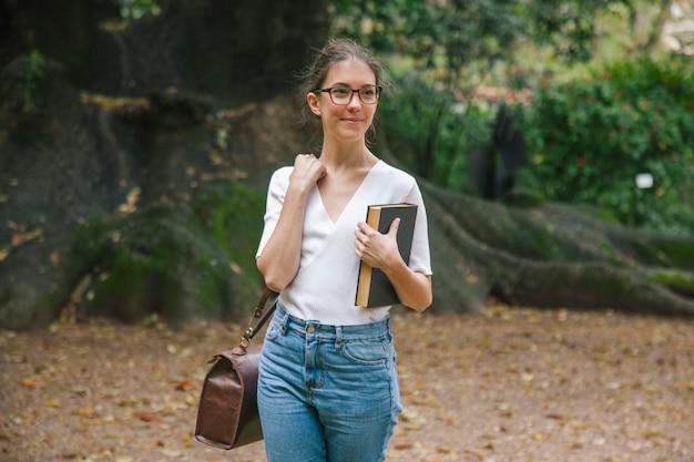 Дружелюбная студентка с учебниками в университете
