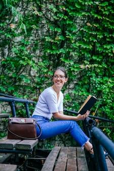 Романтичная молодая женщина учится по книгам на скамейке в колледже