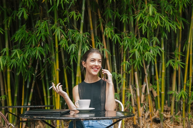 フランスの食堂で彼女の電話に話している陽気な女性