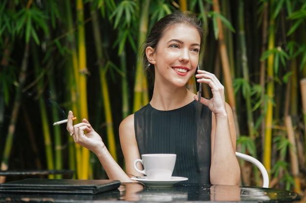 彼女の電話と話している女性、喫煙とコーヒーを飲んで