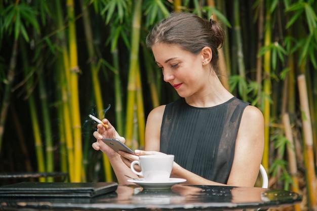 彼女の電話でインターネットを使用して喫煙女性