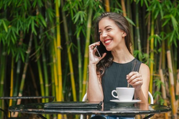 コーヒーテラスで彼女の電話に話しているフランス人女性