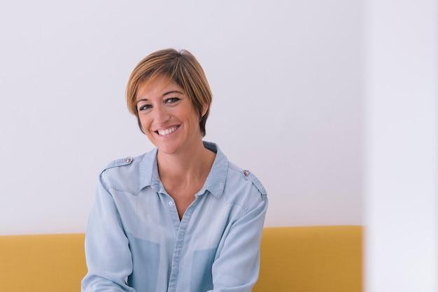 黄色のソファに笑顔の若い女性の肖像画