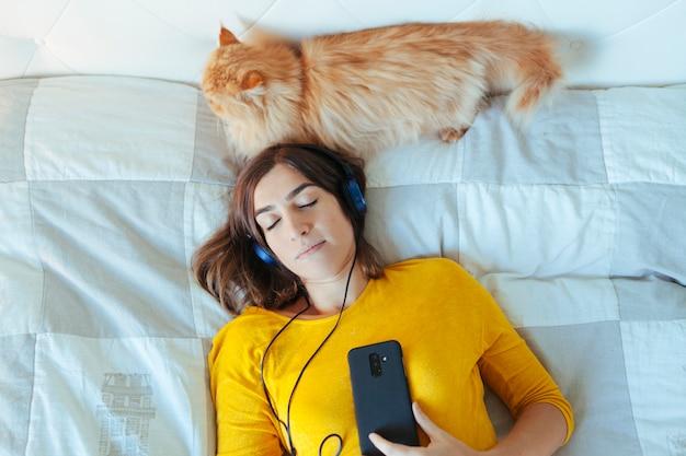 ベッドの上のヘッドフォンをしている女の人