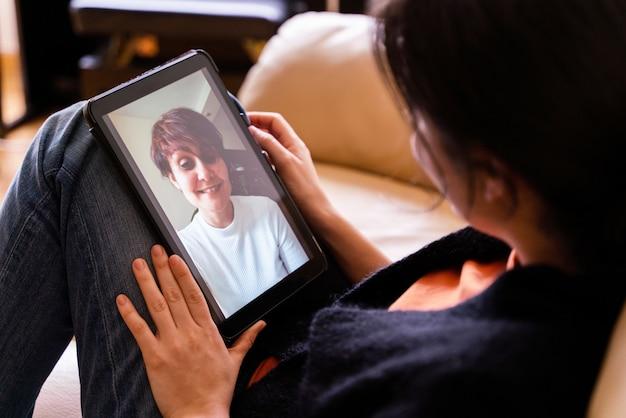陽気な女性がタブレットデバイスで友達に電話します。自宅での隔離隔離における社会的距離の概念。家の中のテクノロジーの人々のライフスタイル。