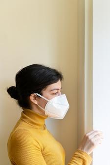 Вертикальный взгляд женщины с проблемами дыхательных легких дома нося защитную лицевую маску.