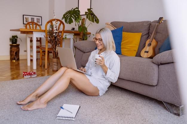 Молодая женщина в очках делает исследовательскую работу для своего бизнеса во время завтрака у себя дома