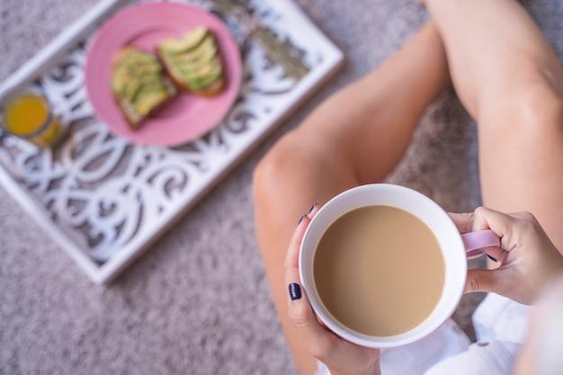 健康的なバランスの朝食を持つ床に座っている女性の手で一杯のコーヒーのクローズアップ