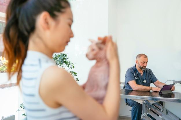 獣医の年の診察でエキゾチックなスフィンクス猫とアジアの女性。腕を抱えて女性は避難所猫を採用しました。