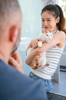 Китайская молодая женщина держа и позаботясь о ее домашняя кошка. образ жизни любителей животных.