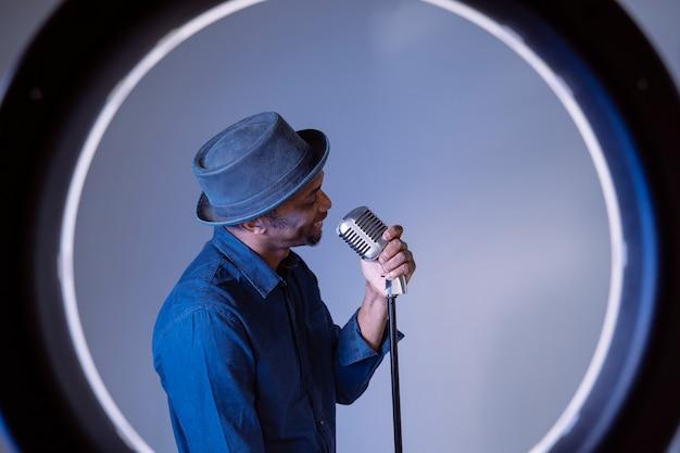 Молодой певец афроамериканца держа ультрамодный микрофон. составьте и создайте текст. портрет битник привлекательный черный человек петь старинные песни. изолированный мужчина выполняя этнические культурные песни.