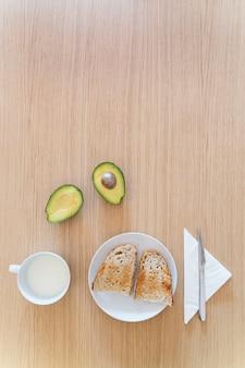 健康食品と朝食でテーブルの垂直平面図です。伝統的なパンのアボカドトーストと新鮮な牛乳。