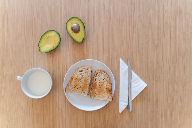 健康食品で調理した朝食のテーブルの平面図です。伝統的なパンのアボカドトーストと新鮮な牛乳。