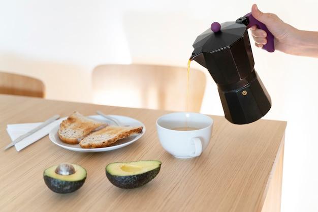 で新鮮なホットコーヒーを注ぐコーヒーポットを保持している女性の手。