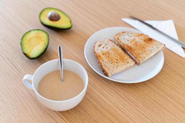 健康食品で調理した朝食のテーブルの側面図です。新鮮なアボカドトースト、オレンジジュース、ラテコーヒー。