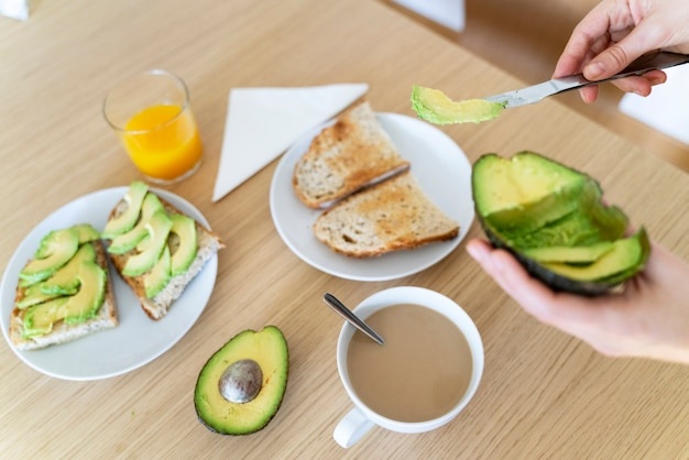 新鮮なアボカドトーストを準備する女性。朝食で包丁を持っている手の平面図です。
