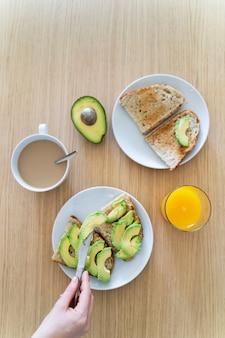 健康食品で調理した朝食のテーブルの平面図です。新鮮なアボカドトースト、オレンジジュース、ラテコーヒー。