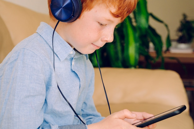 Умный мальчик слушая к музыке с наушниками мобильного телефона звукоизоляционными дома.