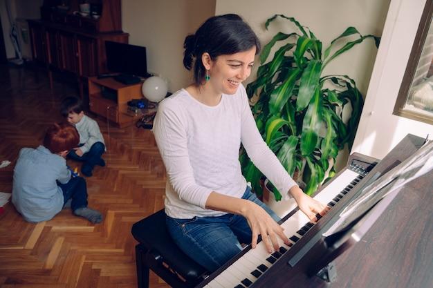 Мама пытается играть на пианино дома, одновременно ухаживая за непослушными детьми, чем хочет играть.