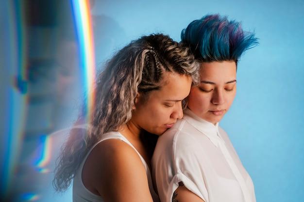 Настоящая пара лесбиянок обниматься с символическим символом радуги лгбт. этническая гомосексуальная молодая женщина собирается поцеловать красивую панк-женщину с голубой прической ирокезом.