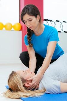 Беременная женщина, имеющая массаж шеи в оздоровительном центре.