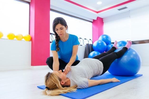 Обученный физиотерапевт, преподавание баланса тела для беременной женщины.