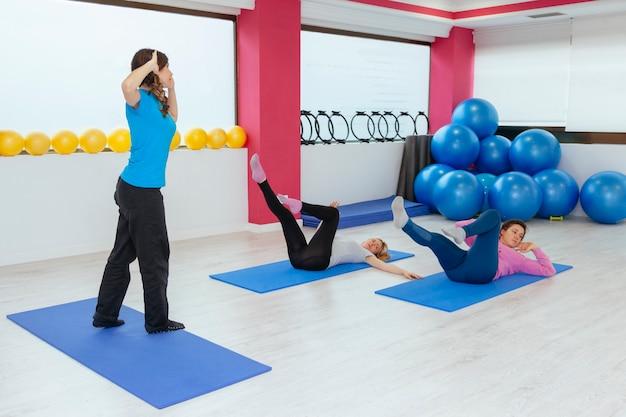 Группа молодых женщин делает упражнения в тренажерном зале