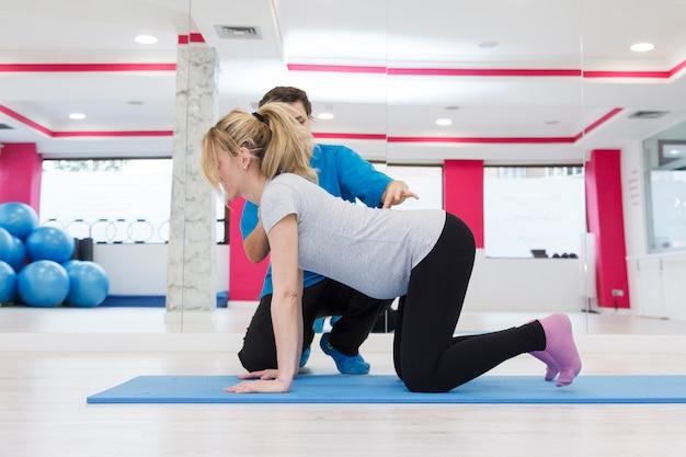 Физиотерапевт делает поясничные упражнения на беременную женщину