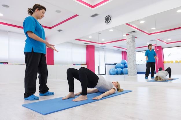 Здоровый инструктор обучает дыхательным упражнениям в период беременности