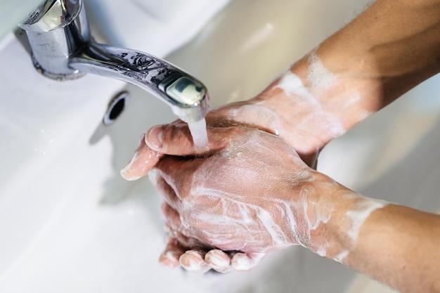 男がトイレで石鹸で手を洗う。個人の衛生状態。パンデミック時の消毒と予防策